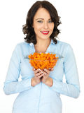 Young Woman Holding a Bowl of Carrots. A DSLR royalty free image, of an attractive young woman, holding a serving dish full of cooked carrots, looking relaxed Royalty Free Stock Photo