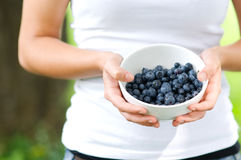 Young woman holding bowl filled blueberries. Fresh blueberries - young woman holding bowl filled blueberries Royalty Free Stock Photos