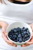 Young woman holding bowl filled blueberries. Fresh blueberries in white bowl Stock Photos