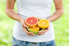 Young woman holding bowl filled oranges and grapefruits. Bowl filled oranges and grapefruits Stock Photos