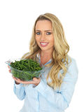 Young Woman Holding a Bowl of Freshly Cooked Green French Beans. Attractive, happy and healthy, young woman, with long blonde hair in her late twenties, holding royalty free stock photo