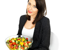 Young Woman Holding a Bowl of Healthy Salad. A DSLR image of an Attractive Young Woman Holding a Bowl of Mixed Salad, looking up at camera, showing healthy Stock Photos