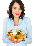 Young Woman Holding a Bowl of Mixed Vegetables. A DSLR royalty free image, of an attractive young woman, holding a serving bowl full of steamed vegetables stock photo
