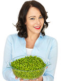 Young Woman Holding a Bowl of Peas. A DSRL royalty free image, of an Attractive young woman holding a serving dish full of green peas, looking relaxed happy and stock photography