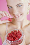 A Young Woman Holding A Bowl Of Raspberries Stock Photos