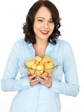 Young Woman Holding a Bowl of Roast Potatoes Stock Photography