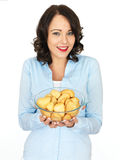 Young Woman Holding a Bowl of Roast Potatoes Royalty Free Stock Images