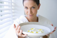 Young woman holding bowl of rose flower petals, smiling, portrait Stock Image