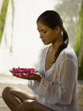 A young woman holding a bowl of rose petals royalty free stock photography