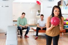 Young Woman Holding Bowling Ball in Club Royalty Free Stock Image