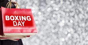 Young woman holding boxing day shopping bag on silver bokeh royalty free stock photos
