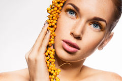 Young woman holding branch of sea buckthorn Royalty Free Stock Photos