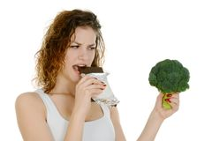 Young woman holding broccoli and chocolate, eating chocolate Stock Photo