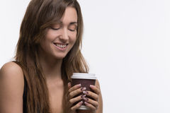 Young woman holding brown cup of coffee. Young woman holding a brown paper of coffee to go Royalty Free Stock Photography