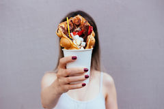 Young woman holding bubble waffle with fruits, chocolate and marshmallow, selective focus Stock Image