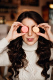 Young woman holding a bunch of colorful macaroons around her face and with on her mouse on blurred background, close-up Royalty Free Stock Photos