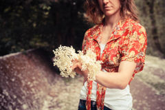 Young woman holding a bunch of elderflowers Stock Photo
