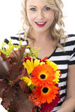 Young Woman Holding a Bunch of Flowers Royalty Free Stock Photography
