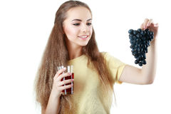 Young woman holding a bunch of grapes and a glass of juice isola Royalty Free Stock Images