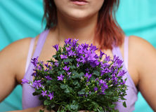 Young woman holding bunch of violet flowers Royalty Free Stock Photography