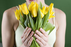 A young woman holding a bunch of yellow tulips, close-up Royalty Free Stock Photo