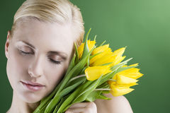 A young woman holding a bunch of yellow tulips, eyes closed Stock Photos
