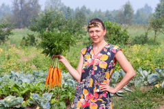 Young woman holding a bundle of carrots Royalty Free Stock Photography