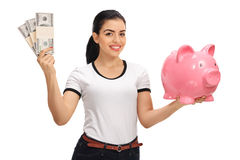 Young woman holding bundles of money and piggybank. Young woman holding bundles of money and a piggybank isolated on white background Royalty Free Stock Photography