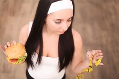 A young woman holding a burger and a measuring tape. A girl stands on a wooden background. The view from the top. The concept of h Royalty Free Stock Photo