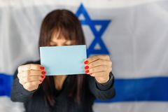 Woman Holding Business Card, Blank Ballot, Voting Paper Front Of Face on Israeli Flag Background. Space for text,mockup. stock image
