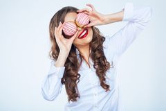 Young woman holding cake in front of eyes. Stock Images