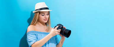 Young woman holding a camera. On a blue background Stock Photos