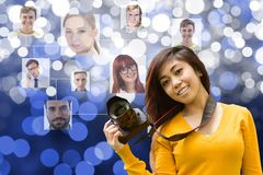 Young woman holding a camera in front of organization chart Royalty Free Stock Photography