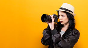Young woman holding a camera. On a yellow background Royalty Free Stock Images