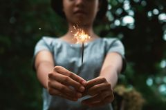 Young woman holding candle firework. And green background royalty free stock photography
