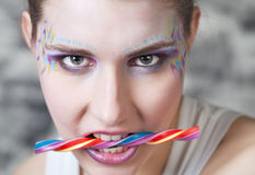 Young woman holding candy in her teeth Stock Photography