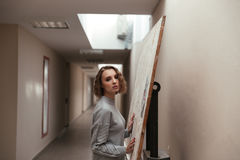 Young woman holding canvas on the easel. Young pretty woman holding canvas on the easel and looking camera Royalty Free Stock Images