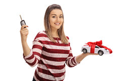 Young woman holding a car key and a model car Stock Images