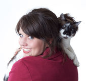 Young woman holding cat, isolated. Young woman holding a cat while looking back over her shoulder; isolated on a white background Stock Photos