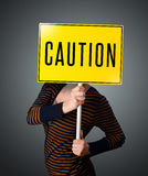 Young woman holding a caution sign Stock Photography