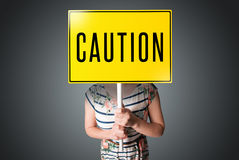 Young woman holding a caution sign Royalty Free Stock Photo