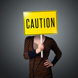 Young woman holding a caution sign Royalty Free Stock Images
