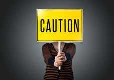 Young woman holding a caution sign Royalty Free Stock Photography