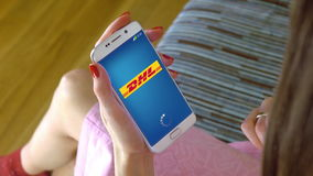 Young woman holding a cell phone with loading DHL mobile app. Conceptual editorial CGI Stock Images