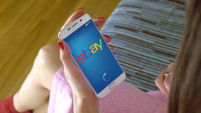 Young woman holding a cell phone with loading Ebay mobile app. Conceptual editorial CGI Stock Photo