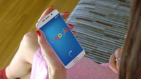 Young woman holding a cell phone with loading Google mobile app. Conceptual editorial 4K clip