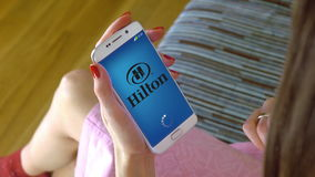 Young woman holding a cell phone with loading Hilton mobile app. Conceptual editorial CGI Stock Photography