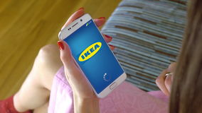 Young woman holding a cell phone with loading Ikea mobile app. Conceptual editorial CGI Royalty Free Stock Photos