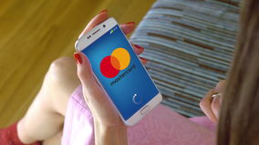 Young woman holding a cell phone with loading Mastercard mobile app. Conceptual editorial CGI Stock Image