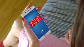 Young woman holding a cell phone with loading Wells Fargo mobile app. Conceptual editorial 4K clip